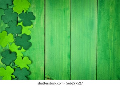 St Patricks Day side border of paper shamrocks over a green wood background