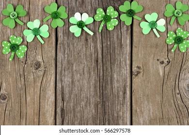 Bordure supérieure du Jour des Saint-Patrick de shamcires en papier fait à la main sur fond bois rustique