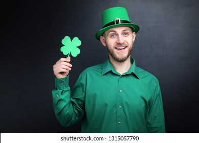 St. Patrick's Day. Young man wearing green hat with paper clover on black background