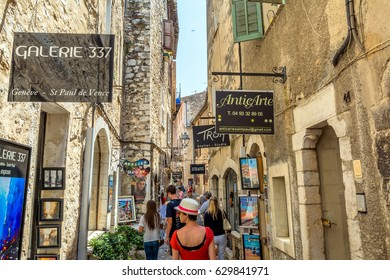 St Paul de Vence, France - June 30, 2016: typical narrow street with tourists and art shops in St Paul de Vence, France. It is a popular destination for a large number of artists, poets and writers
