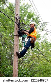 ST PAUL, MINNESOTA - JUNE 05, 2015: Cable man installing modern fiber optic cable to wooden telephone pole