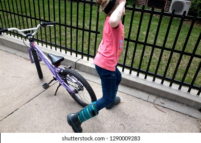 ST PAUL, MINNESOTA / USA - APRIL 16, 2016: Young girl impulsively leaps off bicycle and runs toward fence. Why? it's just what kids do.