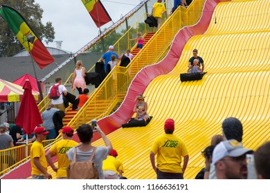 ST. PAUL, MINNESOTA, USA - AUGUST 26, 2018: A couple enjoys a ride with their daughters down the Giant Slide at the Minnesota State Fair in the summer of 2018