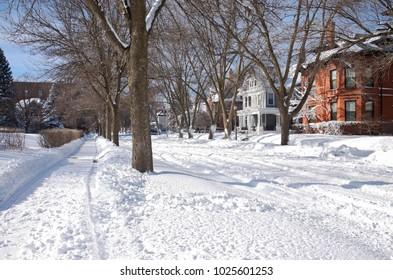 ST. PAUL, MN/USA – JANUARY 23, 2018: Snowy city streets of Saint Paul along Portland Avenue in Historic Hill District of Summit University neighborhood.
