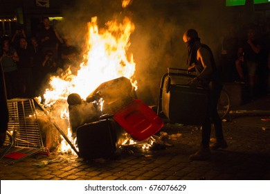 """St. Pauli/Hamburg - Germany July 6, 2017: Protestant throwing a garbage bin into a burning street blockade in front of the """"Rote Flora""""."""
