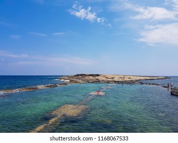 ST. PAUL'S BAY, MALTA - AUGUST 06, 2018: people relaxing and swimming on a beautiful rocky beach in St. Paul's Bay on a sunny day. There is also an abandoned ship on the shore.