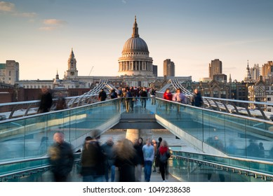 St Pauls Cathedral and the Millennium Bridge at sunset landscape with blurred tourists