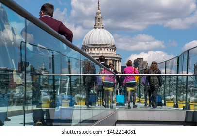 St Pauls  London  United Kingdom  -12 May 2019: Many Tourists Crossing Millenium Bridge with St Pauls Cathedral in Background