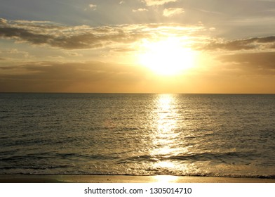 St. Pete Beach, FL, January 22, 2019: Here's a pretty image of the sun and golden skies before sunset, reflected on the steel gray Gulf waters and wet sand at the water's edge on St. Pete Beach.