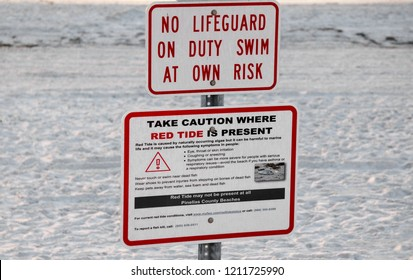 St. Pete Beach, Florida, October 24, 2018: Warning signs for red tide and rip currents are posted prominently at the entrance to St. Pete Beach, Florida.