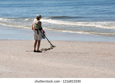 St. Pete Beach, Florida, October 29, 2018: A senior woman walks the beach with a metal detector searching for buried treasures.