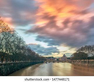 St. Peter's cathedral and Tiber river with high water at evening with dramatic sunset sky. Saint Peter Basilica in Vatican city with Saint Angelo Bridge in Rome, Italy