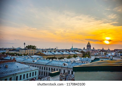 ST. PETERSBURG - August 2018: Roofs of St. Petersburg downtown, view of old houses roofs from the height, St. Petersburg, Russia. View of Saint Isaac's Cathedral from the roof on sunset.
