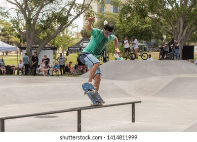 St. Petersburg, Florida / USA - June 1, 2019: Young Man Doing a Rail Slide with His Skateboard at the St.Petersburg Regional Skatepark
