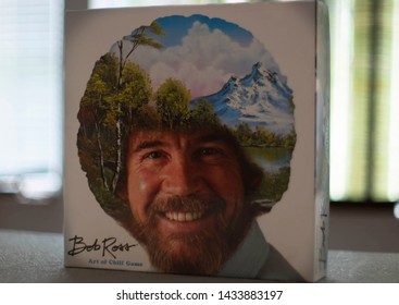 St. Petersburg, Florida / USA - June 2019: Bob Ross board game, 'The Art of Chill', standing upright on a table. Paint majestic mountains and happy trees with Bob and friends in this chill game.