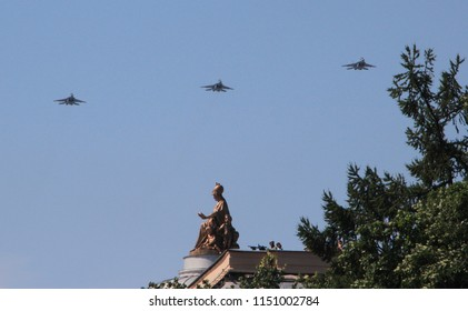 St. Petersburg. Russia. Сombat aircraft flying over the city for air show during  main naval parade on Russian Navy Day. In the foreground Minerva sculpture on the roof of Academy of Arts