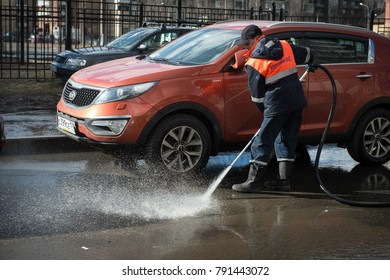 St. Petersburg, Russia - April 8, 2017: A male utility employee washes the roadside where cars are parked.