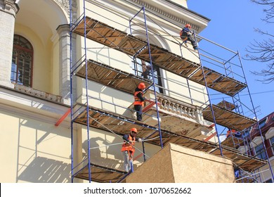 ST. PETERSBURG, RUSSIA - APRIL 9, 2018: Facade Reinovations of Historical Old City Church. Construction Workers on Scaffolding Wearing Bright Orange Uniform Plastering Historical Church Walls.