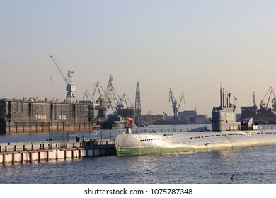 ST. PETERSBURG, RUSSIA - APRIL 9, 2018: Submarine Ship in Industrial Navy Port Docks with Cranes. Russian Military Submarine on Neva River Water at Military Naval Port with Several Cranes Background.