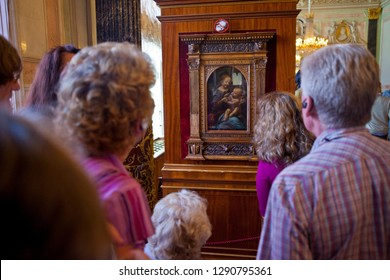 St. Petersburg, Russia - August 16th 2011: Visitors looking at the painting entitled Madonna and Child with Flowers by Leonardo Da Vinci, on display at the Hermitage Museum in St. Petersburg, Russia.