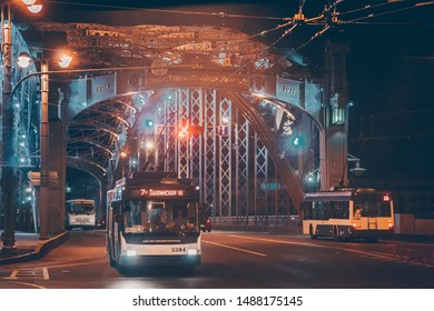St. Petersburg / Russia - August 20 2019: Trolley bus (modern city transport vehicle) crossing the The Bridge of Peter the Great at night.