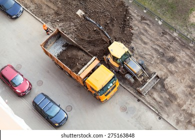 ST. PETERSBURG, RUSSIA - CIRCA APR, 2015: Communal service machinery makes urban land improvement in Russia apartment courtyard. Creation of living environment in city
