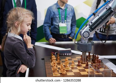 ST. PETERSBURG, RUSSIA - DECEMBER 27, 2018: Robot playing chess with a girl during World Rapid and Blitz Chess Championship 2018. The robot simultaneously plays on 3 chess boards