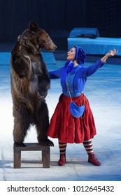 ST. PETERSBURG, RUSSIA - DECEMBER 28, 2017: Victoria Akimova as Gerda with trained bear in the circus show Snow Queen by Great Moscow circus. The show created by Zapashny brothers circus