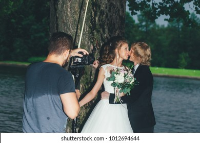 ST PETERSBURG, RUSSIA - JULY 15, 2016: Wedding Event Day. Wedding Couple Bride and Groom at a Wedding Walk. Videographer is Shooting Newlyweds