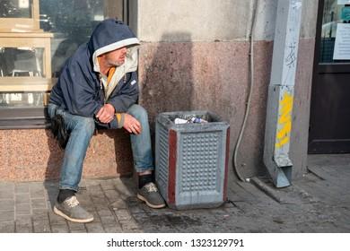 St. Petersburg, Russia - July 20, 2017: Homeless. Sits near the urn. Despair.