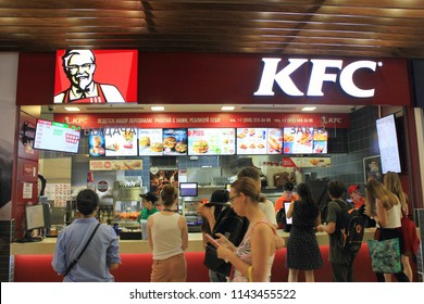 ST. PETERSBURG, RUSSIA - JULY 25, 2018: KFC Fast Food Restaurant with Customers. Kentucky Fried Chicken (KFC) Fast Food at Mall Food Court with Brand Logo and People Waiting in Line to Order.