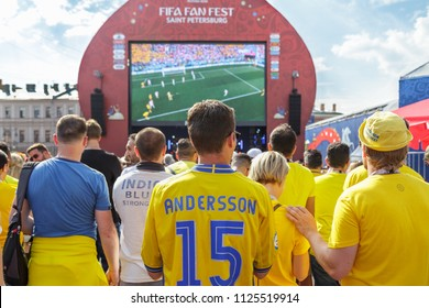 St. Petersburg, Russia - June 18, 2018: Supporters of Sweden national football team watching game match on large screen at fan festival. FIFA World Cup. Swedish fans, back view. People, crowd.