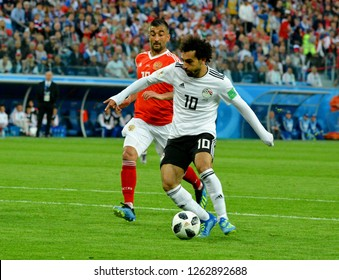 St Petersburg, Russia - June 19, 2018. Egyptian football star Mohamed Salah against Russia national team midfielder Alexander Samedov during World Cup 2018 match Russia vs Egypt.