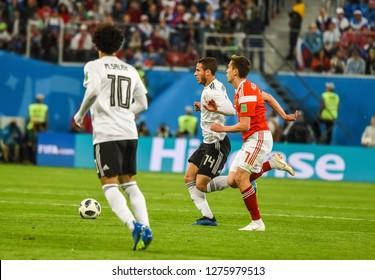 St Petersburg, Russia - June 19, 2018. Egypt national team striker Ramadan Sobhy against Russia national team midfielder Daler Kuzyaev during World Cup 2018 match Russia vs Egypt.