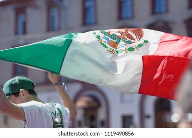 ST. PETERSBURG, RUSSIA - JUNE 20, 2018: Mexican football fan with national flag at FIFA Fan Fest in Saint Petersburg during FIFA World Cup Russia 2018. The city host 7 matches of FIFA World Cup
