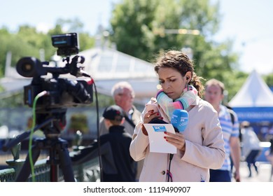 ST. PETERSBURG, RUSSIA - JUNE 20, 2018: Journalist of France 24 prepares to reportage at FIFA Fan Fest in Saint Petersburg during FIFA World Cup Russia 2018. The city hosts 7 matches of FIFA World Cup