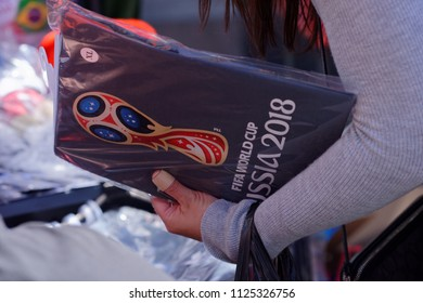 ST. PETERSBURG, RUSSIA - JUNE 20, 2018: Football fan buying photo album with logo of FIFA World Cup Russia 2018. The city host 7 matches of FIFA World Cup