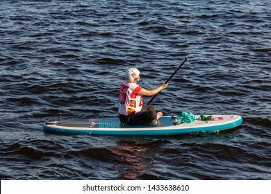 St. Petersburg, Russia - June 23, 2019: girl rowing paddle sitting on the SUP board. training rowing on the Neva River urban water activities