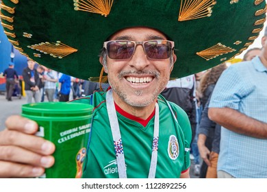 St. Petersburg, Russia - June 25, 2018: Close-up portrait of cheerful football fan from Mexico, dressed in sombrero, with glass of beer in hand during 2018 FIFA World Cup.