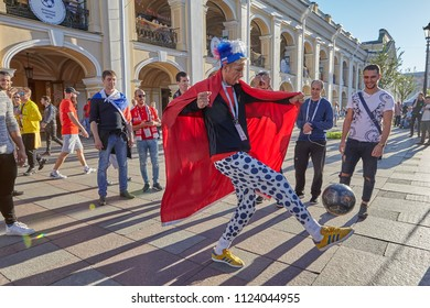 St. Petersburg, Russia - June 25, 2018: Russian football fan in stupid hat with tricolor and ridiculous clothes, kicks ball on Nevsky Prospekt in Saint-Petersburg.