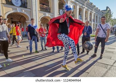 St. Petersburg, Russia - June 25, 2018: Russian football fan in stupid hat and funny clothes, kicks ball on Nevsky Prospekt in Saint Petersburg.