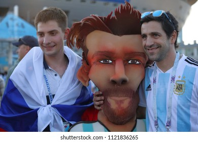 ST. PETERSBURG, RUSSIA - JUNE 26, 2018: Argentinian and Russian football fans at a cartoon of Lionel Messi near Saint Petersburg stadium during FIFA World Cup 2018 before the match Argentina - Nigeria