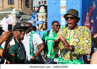 St. Petersburg, Russia - June 26, 2018: Soccer fan of Nigeria national football team at FIFA World Cup. Group of nigerian supporters before match outside. African men celebrating with vuvuzela.