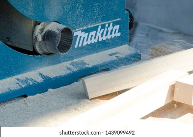 St. Petersburg, Russia - June 6, 2019: Smooth pine wood bars on a pile of sawdust. Pipe from a circular sawing table Makita, shavings fly. Concept of carpentry, woodworking, handmade, male hobby