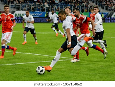 St Petersburg, Russia - March 27, 2018. French striker Kylian Mbappe making a dangeous cross with Russian players Roman Neustaedter and Aleksandr Samedov in the background.