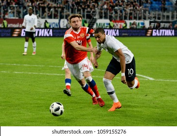 St Petersburg, Russia - March 27, 2018. Russian centre-back Vladimir Granat against French striker Kylian Mbappe during Russia vs France match in St Petersburg.
