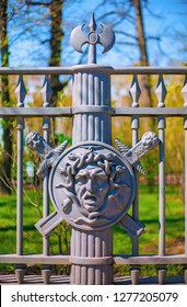 ST. PETERSBURG, RUSSIA - MAY 15, 2013: Fragment of a metal fence of the Summer Garden decorated with the image of the face of the Gorgon Medusa on the background of a shield and swords
