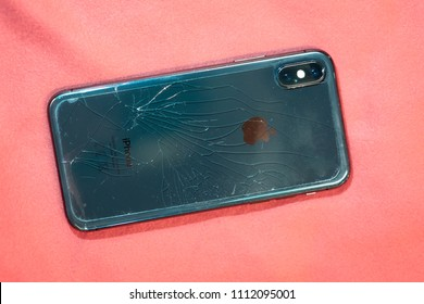 ST. PETERSBURG, RUSSIA - MAY 27, 2018: Black smartphone Iphone X broken glass on the back cover of the phone close up