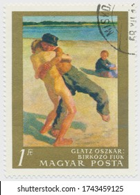 ST. PETERSBURG, RUSSIA - MAY 28, 2020: A postmark printed in HUNGARY, shows painting Wrestling Boys by Oszkar Glatz (1872-1958), circa 1967