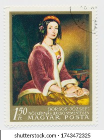 ST. PETERSBURG, RUSSIA - MAY 28, 2020: A postmark printed in HUNGARY, shows painting Lady in Fur-lined Jacket by Jozsef Borsos (1821-83)., circa 1967